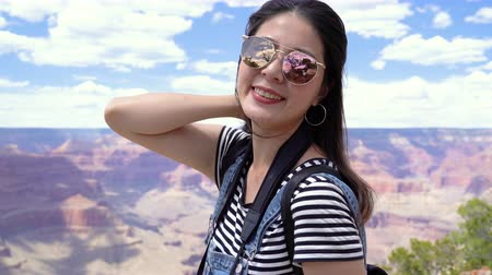 arenito : wind blowing beautiful female asian backpacker black hair. young girl flicks hair face camera smiling standing on the top of desert mountain grand canyon national park. charming lady wear sunglasses