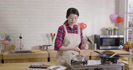 домохозяйка : wife in apron standing in modern wooden kitchen breaking dark chocolate into pieces. asian female chef baker mixing sweet delicious organic melted cocoa cream in bowl in hot pot on stove stirring.