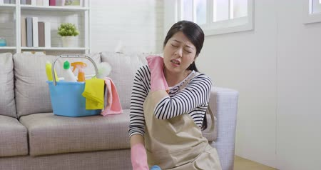 sanitize : young female household with painful neck frowning sitting on floor massage shoulder. too much overwork housekeeping cause body unwell healthcare. cleaning supplies in bucket on sofa.