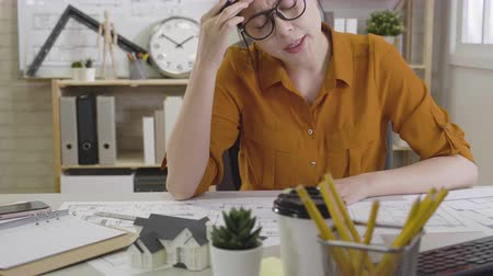хмурый : young girl interior designer suffering from headache while drawing blueprint at desk in office. asian woman architect using pencil working on floor plan feeling head hurt shaking head to release pain