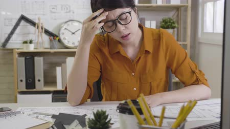 хмурый : slow movement of asian female interior designer frowning hands hold pencil touching head suffering from headache while working on floor plan on drawing board. sick woman architecture sit in office
