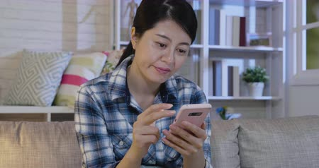 human interest : slow motion of young female people having boring conversation on smart phone putting away relaxing on couch at late night in cozy apartment. asian woman holding cellphone not interest in internet. Stock Footage