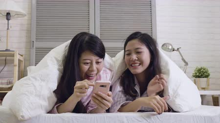 paplan : slow motion of two chinese female roommates lying on front cover body by quilt in comfortable bed talking discussing about mobile phone. young girls chatting holding cellphone looking at screen.