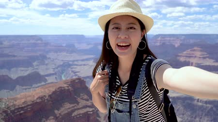 arenito : female hiker taking selfie while out trekking in the wilderness. young girl in straw hat cheerfully recording travel video in desert mountain with blue sky. tourism spot Grand Canyon National Park