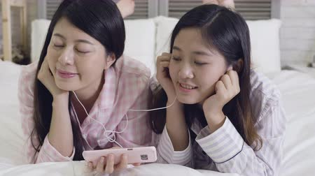wearing earphones : slow motion of young girls in night wears moving heads enjoy melody by earphones. female best friends in pajamas and headphones listening music together lying in bed relaxing holding smartphone.