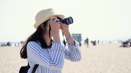 salvaguardar : asian woman tourist photographer taking picture by professional slr camera of skylines in santa monica pier. Female traveler looking view photographing snapshots on beach. lady in hat and sunglasses