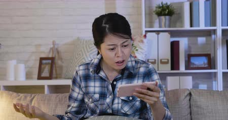 regret : Confused young woman sitting alone on couch in living room at home at night looking at smartphone screen with irritation and indignant. Annoyed lady with error cellphone while watching series online