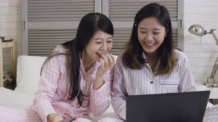 wearing earphones : slow motion two young pretty happy Asian Korean student girls together at home bedroom using internet social media in laptop computer laughing cheerful on bed having fun in women friendship concept. Stock Footage