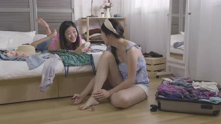 sisters : slow movement of young girls in bedroom relaxing spending time together. asian women chatting laughing one lying on bed using cellphone and one polish nail on feet sitting next to unpacked luggage.