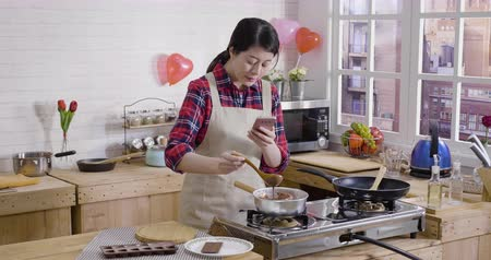 cooking pots : asian female blogger at home using cellphone shoots video cooking process of making handmade chocolate for boyfriend on valentines day showing fans online. young girl stirring dark chocolate on stove