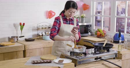 cooking pots : young asian woman holding mobile phone using camera app recording process of making dessert on valentines day. Stock Footage