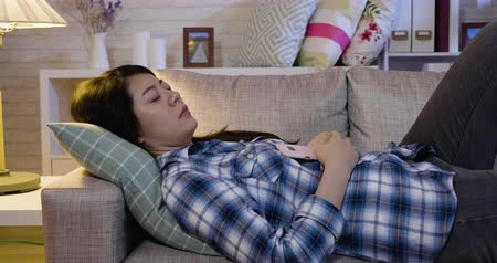 after school : attractive asian woman napping with mobile phone in her hand on sofa at night.