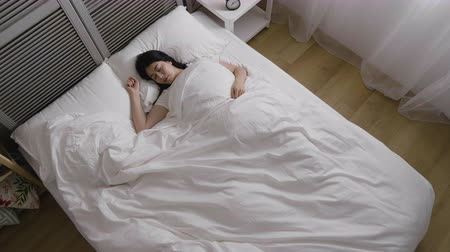 yorgan : top view time lapse of young well sleeping asian woman in warm bed cover by white quilt. cozy white bedroom dark night turn bright in the morning after sunrise. girl stretching wake up smiling.