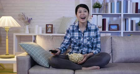 watch tv : slow motion girl watch funny movie. Cheerful woman watching series on TV holding bucket of popcorn while sitting on couch at home in midnight. female college student stay up late with comedy film. Stock Footage