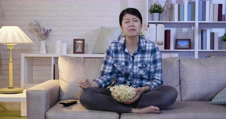 teatral : Emotional lovely girl watching a drama movie eating popcorn at home. sad asian woman crying seeing romantic film on television tv channel sitting on couch in house with junkfood at late night.