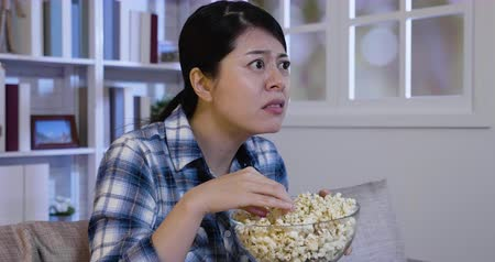 watch tv : Young asian woman at home sofa watching horror movie or suspense thriller film in panic and eating popcorn bowl at night Stock Footage