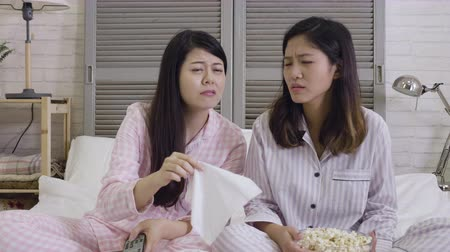 nyomasztó : Two sentimental women friends crying and wiping tears with handkerchiefs while watching dramatic sad movie.