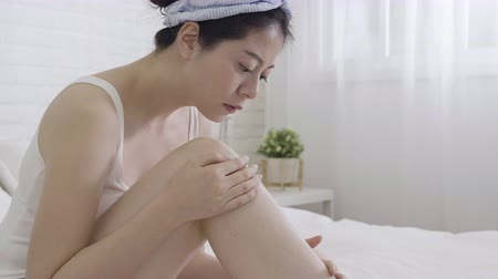 yorgan : slow motion of closeup young woman smearing cream on legs on bed.
