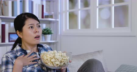 teatral : Surprised woman eating junk food on sofa at home watching horror movie. young asian lady spill popcorn while scared by thriller film. Terrified girl bowl of popcorn sit on couch hand touch heart.