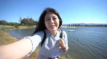 rty : slow action cheerful lady waving hands saying goodbye sending kiss to cellphone while having video phone call. young girl tourist standing on the pier on sunny day. travel in nature near the port.