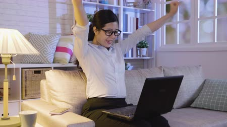 yetiştirmek : slow motion asian businesswoman looking at work on laptop computer with satisfaction and stretching arms in the air staying up late in midnight hard working. young office lady at home cheerful smile