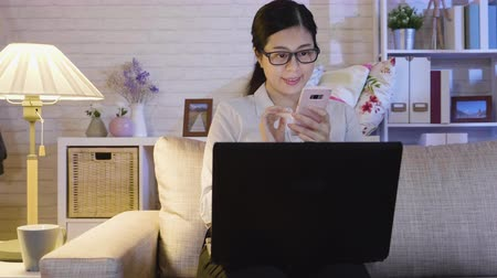 чат : young woman using cellphone chatting online while staying up late working with laptop at home. happy office lady taking a break texting message sitting on sofa in midnight. glasses girl notebook sofa