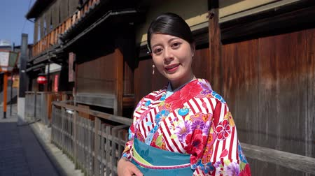 hanamikoji : attractive asian woman wearing kimono walking on old street in ishibe alley in kyoto. young japanese girl in traditional dress face camera smiling lovely standing next wooden house on road suuny day Stock Footage