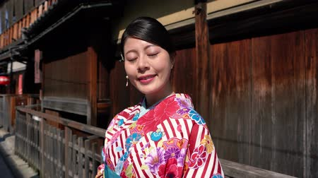 hanamikoji : young traveler with kimono costume standing in old city in Japan face camera smiling attractive. girl tourist in floral kimono clothing with wooden wall Kyoto ishibe alley. asian visitor tour japan