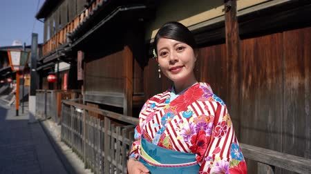 hanamikoji : beautiful lady with flower pattern kimono standing in the old street in Kyoto. young Japanese woman near wooden house in traditional culture dress in Ishibe alley on sunny day smiling lovely. Stock Footage