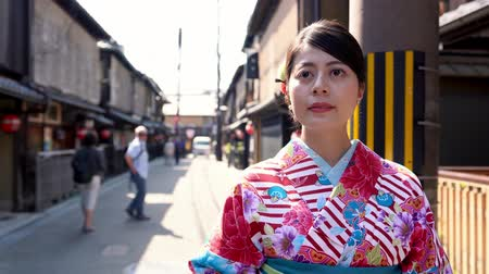 hanamikoji : car driving in old town road in background under sunshine. young japanese lady in floral kimono costume walking in kiyomizu zaka street going to shopping join festival in summer on holidays. Stock Footage
