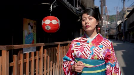 hanamikoji : fast motion old city lifestyle people in kyoto japan. Young happy Asian woman walking on history ancient kiyomizu sannenzaka street wearing flower pattern kimono clothing passing wooden bamboo houses Stock Footage