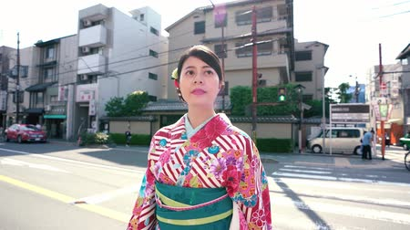 hanamikoji : young elegant tourist woman wearing flower pattern kimono walking on urban road zebra crossing. girl traveler experience japanese culture in traditional dress in busy city street on sunny day. Stock Footage