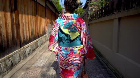tokio : back view of young local woman walking in old town path wearing floral kimono costume going home. japanese lady in traditional costume lifestyle join festival passing through wooden wall in street.