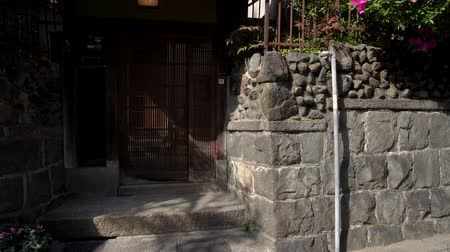 quimono : japanese style design house with wooden door and stone wall road. beautiful young girl in floral kimono traditional costume walking by green garden with trees flowers blooming in spring on sunny day.