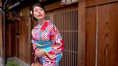 traje de passeio : elegant local woman in flower pattern kimono standing in front of wooden home waiting for friends join festival together. young japanese lady in traditional costume looking around carrying purse.