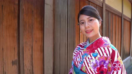 japonsko : young girl wearing floral silk kimono standing near wooden house face camera smiling attractive in ishibe alley kyoto japan on sunny day. elegant japanese woman in colorful traditional dresses joy. Dostupné videozáznamy