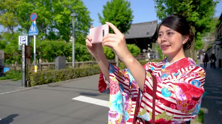 bamboo curtain : travel japan and technology concept from beauty girl in kimono dress hold smart phone support using photographing app. young lady traveler in traditional floral clothing taking picture on street. Stock Footage