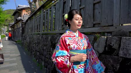 quimono : local lady live in traditional japanese way wearing in colorful lace kimono going to join summer festival walking on street along the rock wall beside. woman in traditional dress in gion hatanaka. Vídeos