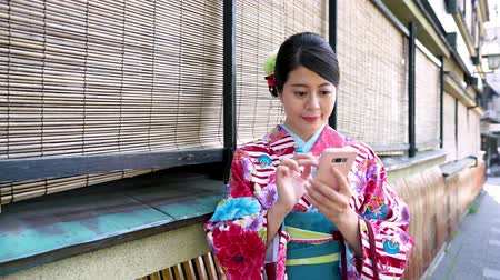 bamboo curtain : young japanese woman texting online message standing near the bamboo curtain. girl in floral traditional dress using mobile waiting in path gion hatanaka on summer festival. lady in kimono smiling .