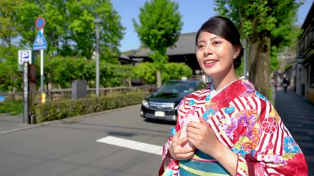 bamboo curtain : cheerfully young japanese lady standing on street in city urban kyoto japan holding cellphone watching beautiful sunset. woman in floral kimono dress on road with car driving through in background.