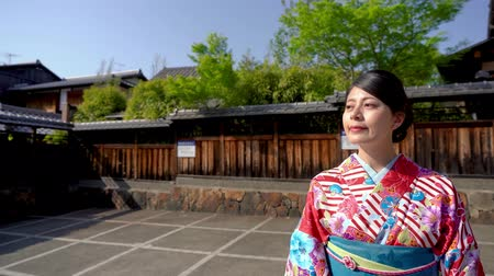 quimono : local woman wearing japanese traditional clothing at Yasaka Pagoda and Sannen Zaka Street in Kyoto Japan after praying in temple. young lady in kimono cardigan standing under blue sky in spring.