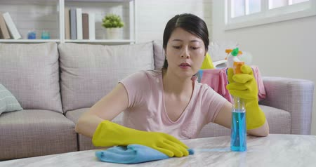 хмурый : unhappy asian korean housewife polishing table in living room by cloth and detergent. tired girl frowning wiping sweat by hand in protective yellow gloves sitting on floor. young wife doing housework Стоковые видеозаписи