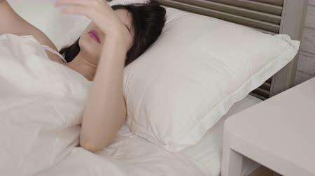 tank top : slow motion of lovely korean girl wake up in the morning taking mobile phone on table lying in bed. woman do first thing open eyes use cellphone check message. young people addiction technology Stock Footage