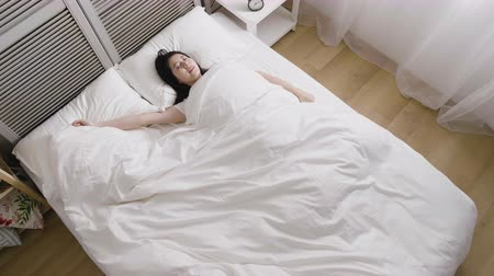 move well : top view of slow motion young asian woman sleeping in bedroom resting and dreaming. charming happy girl wake up stretching in comfort bed in sunshine apartment in morning. female lying cover quilt