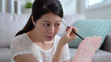 transmissão : Beautiful asian woman is applying eyebrows by brush looking holding mirror sitting on floor in living room at home in apartment. happy young beauty girl makeup prepared in the morning using cosmetic.