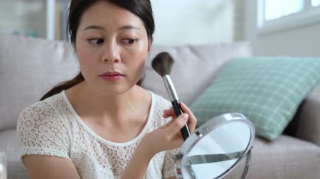 vurgulayıcı : Young beautiful Asian woman professional beauty vlogger doing make up tutorial. beautiful girl using brush applying blush preparing in morning. female blogger applying makeup looking at mirror home