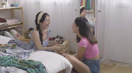 まだ : Smiling girl giving friend makeover doing makeup in the morning at messy room with clothes not yet packing for vacation. 動画素材