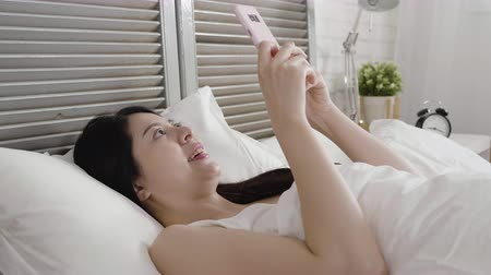 ébresztő óra : Beautiful young woman sleeping on bed comfortably by using smartphone.