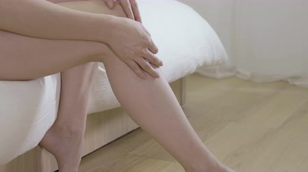 perfect weather : slow motion beautiful asian woman sitting on bed  touching bare legs at home bedroom.