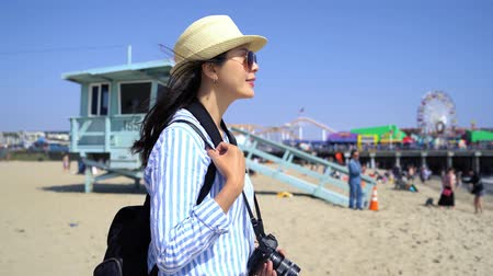 salvaguardar : fast forward of young asian female photographer holding professional dslr camera enjoy ocean view on sandy beach Santa Monica Pier near lifeguard stand.